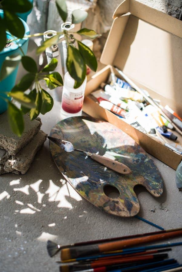 Кисти и сортированные краски на поле студии художника стоковое изображение