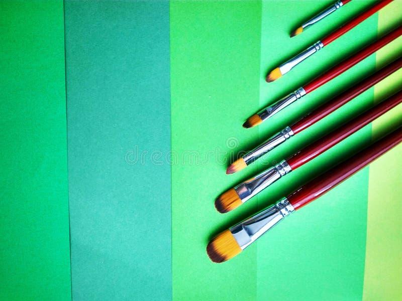 Кисти на предпосылке покрашенной бумаги стоковое фото