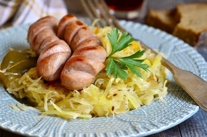 Кислое тушёное мясо капусты с зажаренной сосиской стоковые изображения