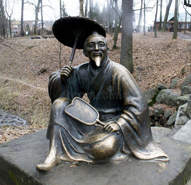 Китаец скульптуры веселый с зонтиком arbutus стоковое фото