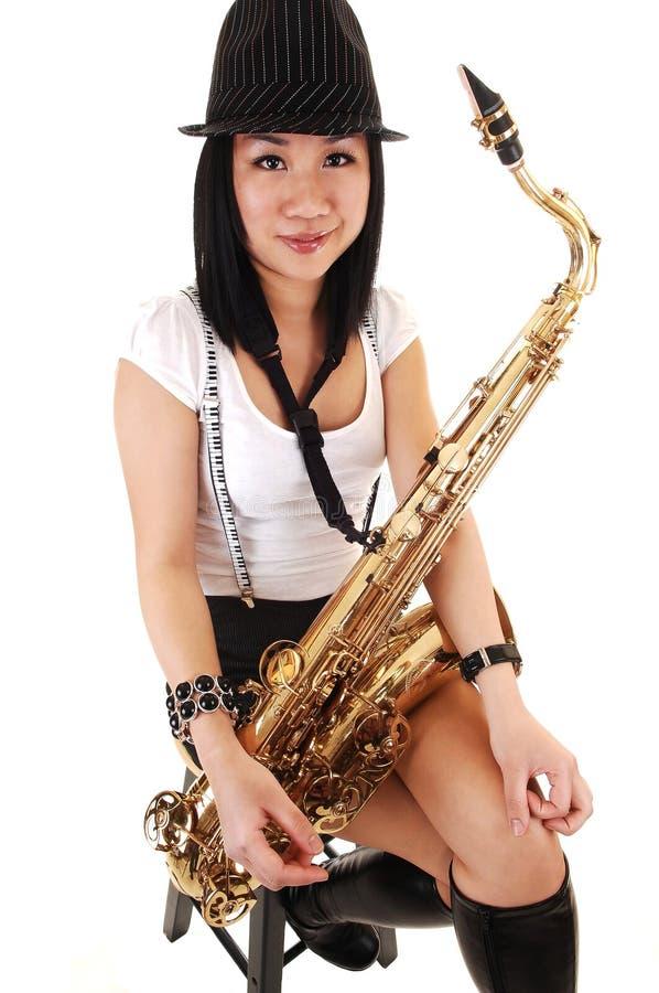 китайская девушка играя саксофон стоковое изображение rf