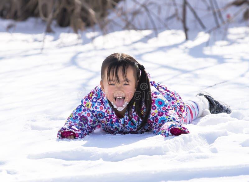 Китайская девушка лежа в снеге стоковое изображение rf