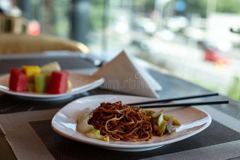 Китайская жареная лапша и палочки для еды Боковая тарелка сельдерея и моркови Китайская капуста Коричневый китайский спагетти с о стоковые изображения