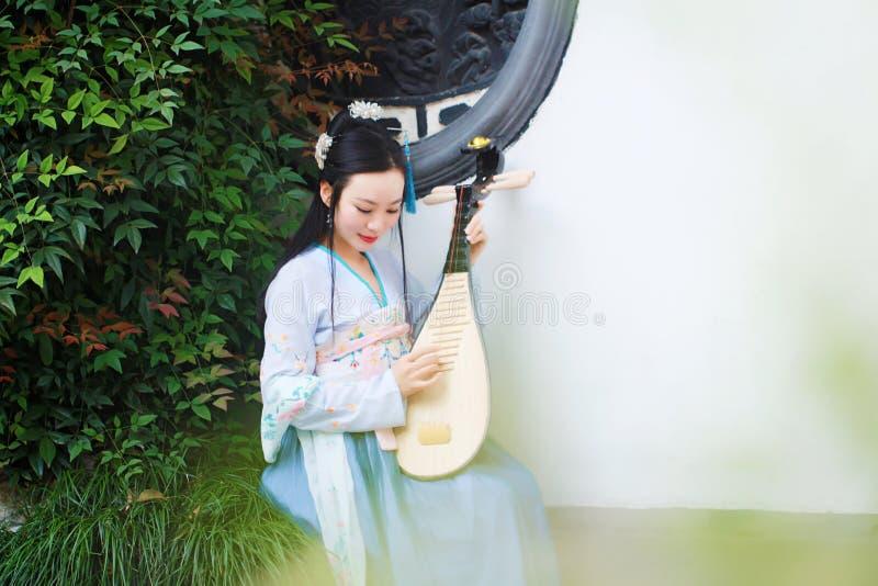 Китайская женщина в традиционном платье Hanfu, играет традиционную аппаратуру пипы стоковое изображение rf