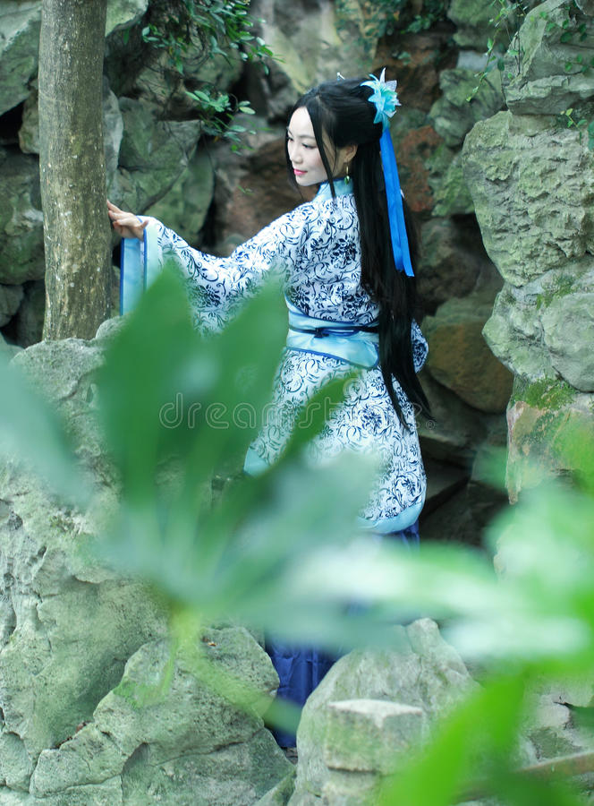 Китайская женщина в традиционном голубом и белом платье Hanfu стоя перед rockery стоковые изображения