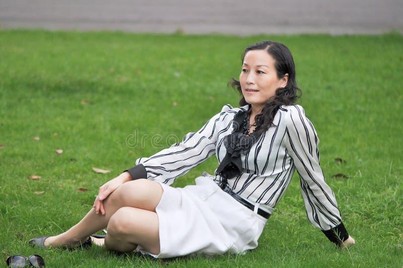 Китайская женщина сидит на траве стоковое фото rf