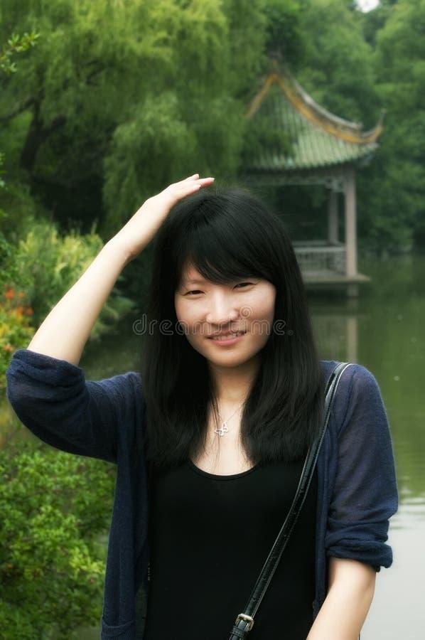 Китайская женщина усмехаясь и patting ее голова стоковые фотографии rf