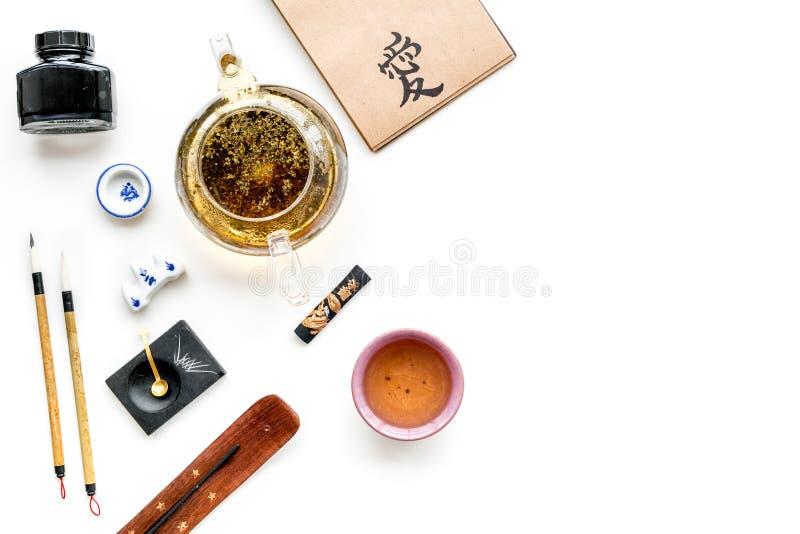 Китайская или японская картина каллиграфии Иероглиф в тетради бумаги ремесла, писать аксессуары, чайник и чашку чаю стоковое фото rf