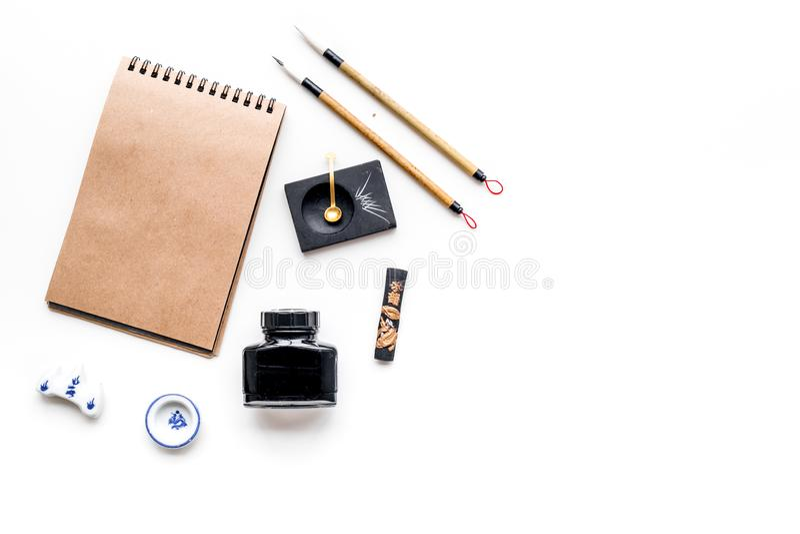 Китайская или японская картина каллиграфии Иероглиф в тетради бумаги ремесла и аксессуарах записи на белой предпосылке стоковые фото