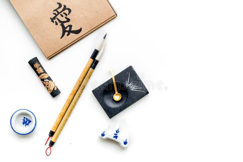 Китайская или японская картина каллиграфии Иероглиф в тетради бумаги ремесла и аксессуарах записи на белой предпосылке стоковое фото rf