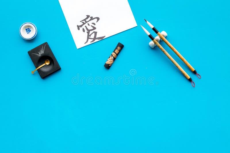 Китайская или японская концепция каллиграфии Иероглиф около традиционных написанных аксессуаров на голубом взгляде сверху предпос стоковая фотография