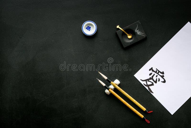 Китайская или японская концепция каллиграфии Иероглиф около традиционных написанных аксессуаров на черном взгляде сверху предпосы стоковое изображение