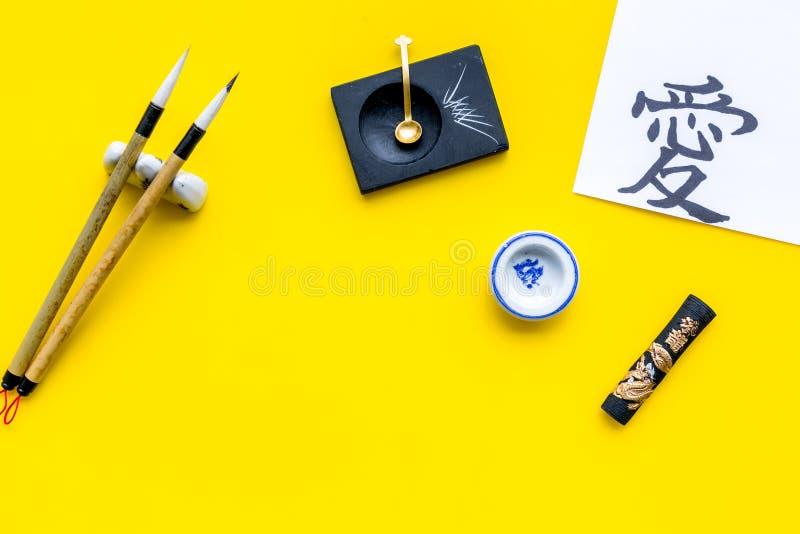 Китайская или японская концепция каллиграфии Иероглиф около традиционных написанных аксессуаров на желтом взгляде сверху предпосы стоковые изображения rf