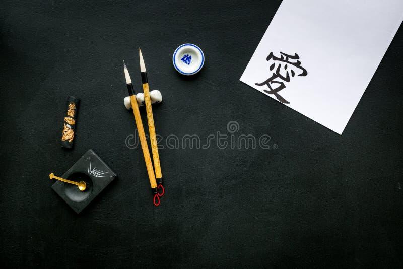 Китайская или японская концепция каллиграфии Иероглиф около традиционных написанных аксессуаров на черном взгляде сверху предпосы стоковое фото