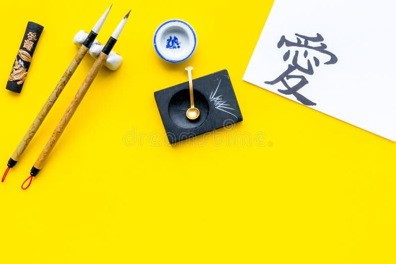 Китайская или японская концепция каллиграфии Иероглиф около традиционных написанных аксессуаров на желтом взгляде сверху предпосы стоковое изображение rf