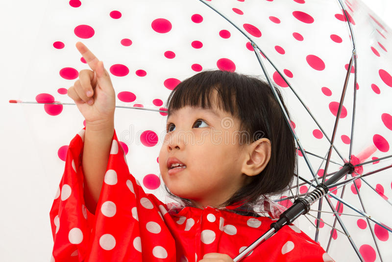 Китайская маленькая девочка держа зонтик с плащом стоковые изображения