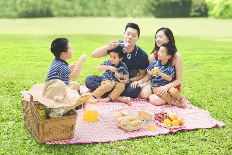 Китайская семья играя с мылом пузыря в парке стоковое фото rf