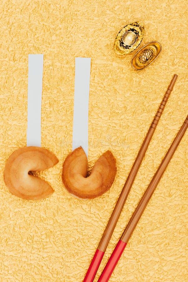 Китайские печенья с предсказанием с палочками и золотыми инготами на золотой поверхности, китайской концепции Нового Года стоковое изображение