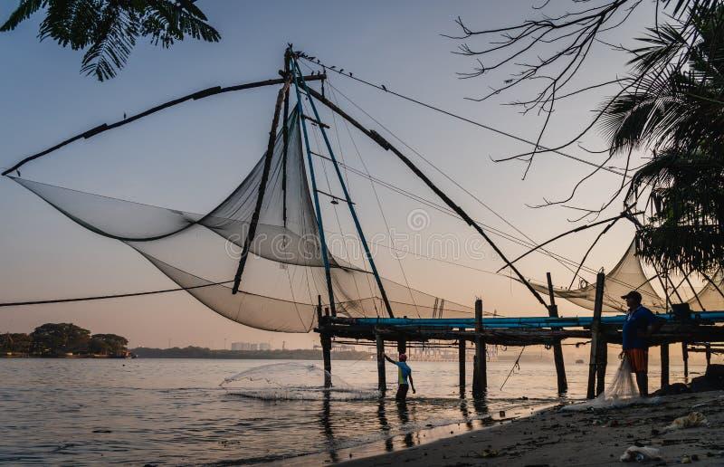 Китайские рыболовные сети во время золотых часов на форте Kochi, работе рыболова восхода солнца Кералы, Индии стоковое изображение rf