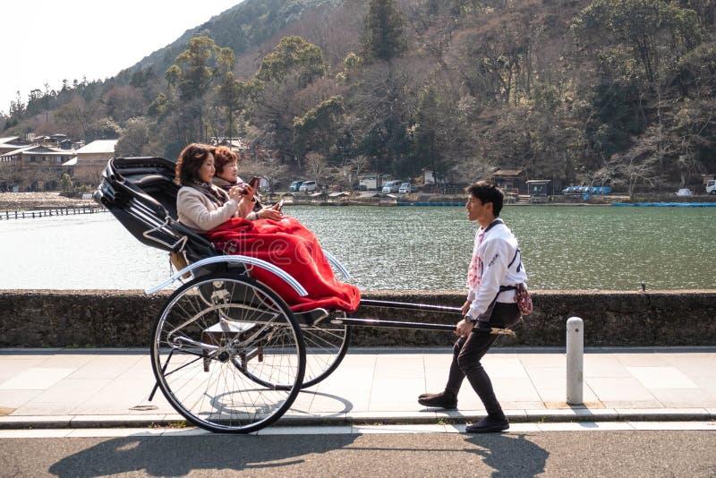 Китайские туристы взошли на борт рикши вытягиванной молодым человеком стоковое фото rf