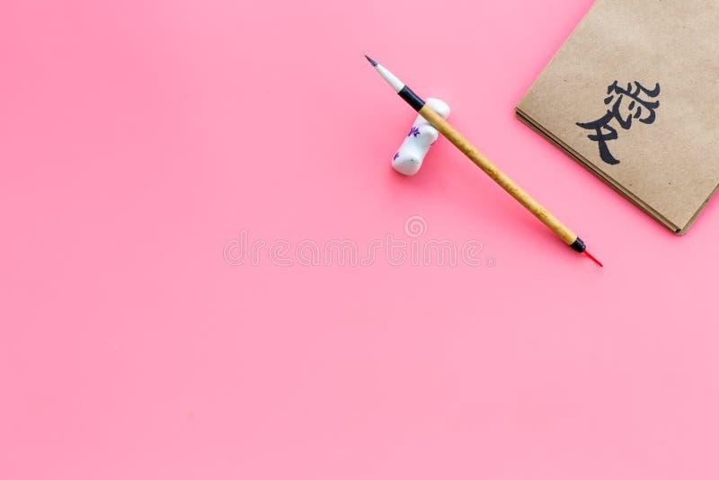 Китайский или японский иероглиф который значит любовь на английском Концепция каллиграфии на розовом космосе взгляда сверху предп стоковая фотография rf