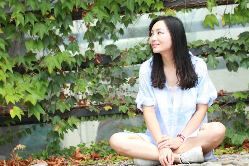 Китайский портрет молодой красивой женщины сидит для того чтобы огородить в парке стоковая фотография rf