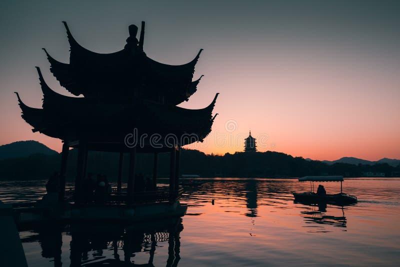 Китайцы благоустраивают на заходе солнца, старом газебо стоковые изображения rf