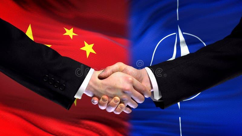 Китай и рукопожатие НАТО, международные отношения приятельства, предпосылка флага стоковые изображения