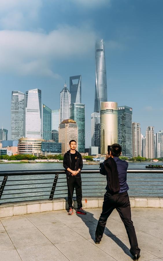 Китай, Шанхай 19-ОЕ АПРЕЛЯ 2019: человек туристов принимает фото в зоне бунда Шанхая стоковая фотография rf