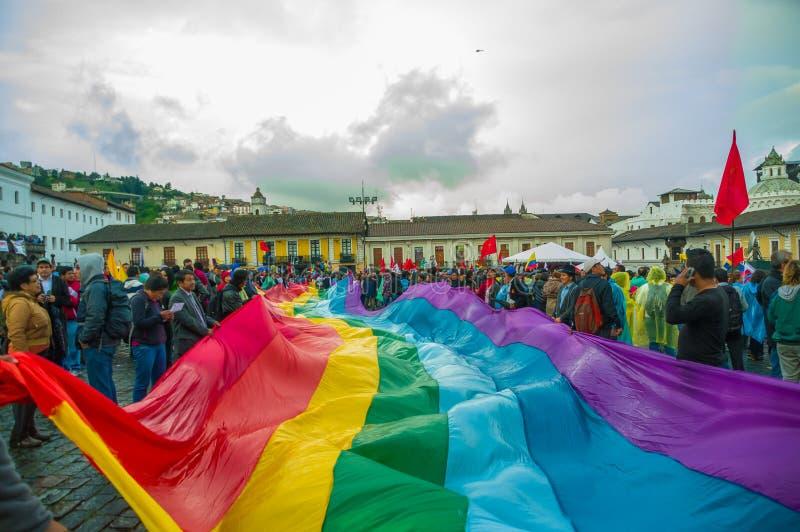 Кито, эквадор - 27-ое августа 2015: Коренной народ с большой радугой покрасил флаг во время массовых демонстраций против стоковая фотография rf
