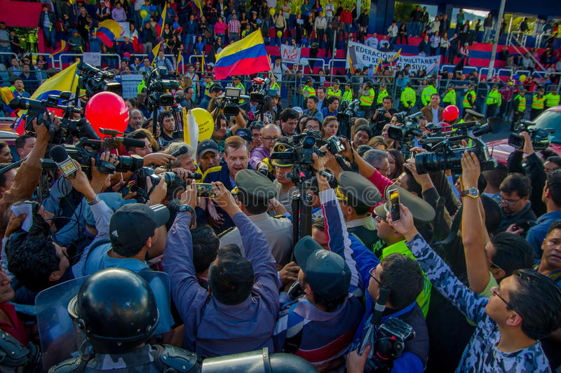Кито, эквадор - 7-ое апреля 2016: Группа людей держа знаки протеста, полиция и журналисты во время анти- правительства стоковое изображение rf