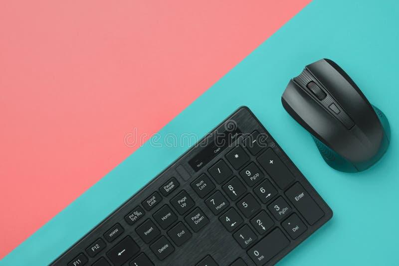 Клавиатура и мышь компьютера черноты взгляда сверху на красочной предпосылке с космосом экземпляра стоковая фотография