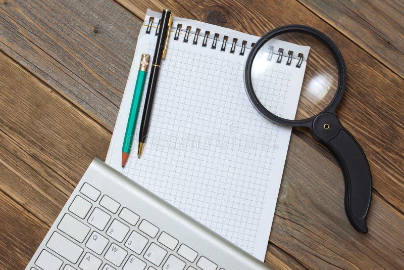Клавиатура компьютера, тетрадь, лупа и карандаш с шариковой ручкой на старом столе Поиск интернета стоковая фотография
