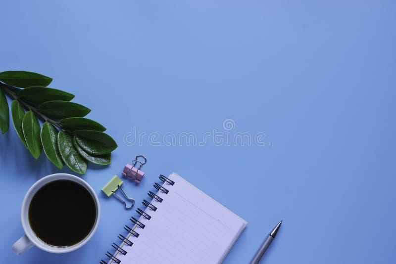 Клавиатура, тетрадь, ручка, или объект взгляда сверху для концепции канцелярские товара на голубой предпосылке стоковое фото