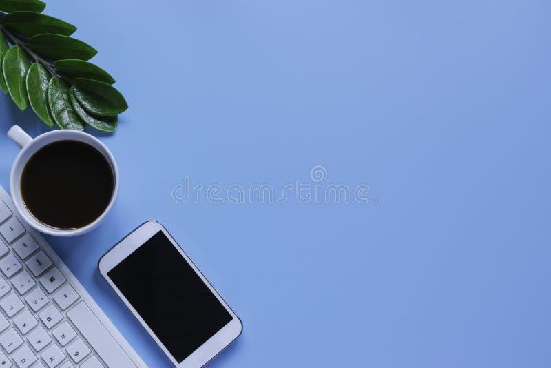 Клавиатура, тетрадь, ручка, или объект взгляда сверху для концепции канцелярские товара на голубой предпосылке стоковые изображения