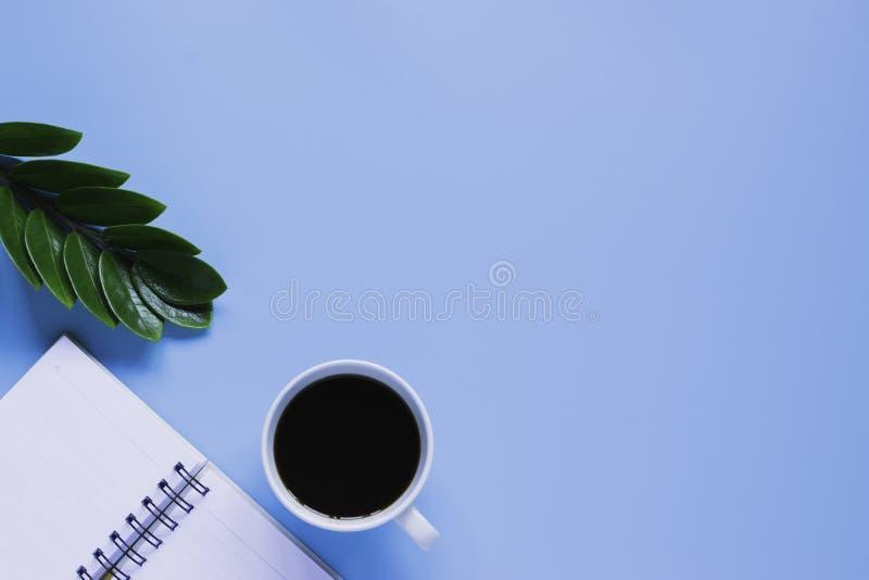 Клавиатура, тетрадь, ручка, или объект взгляда сверху для концепции канцелярские товара на голубой предпосылке стоковое изображение