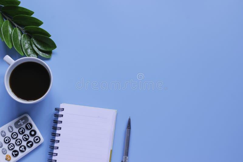 Клавиатура, тетрадь, ручка, или объект взгляда сверху для концепции канцелярские товара на голубой предпосылке стоковые фотографии rf