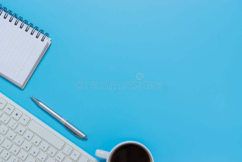 Клавиатура, тетрадь, ручка, или объект взгляда сверху для концепции канцелярские товара на голубой предпосылке стоковое изображение rf