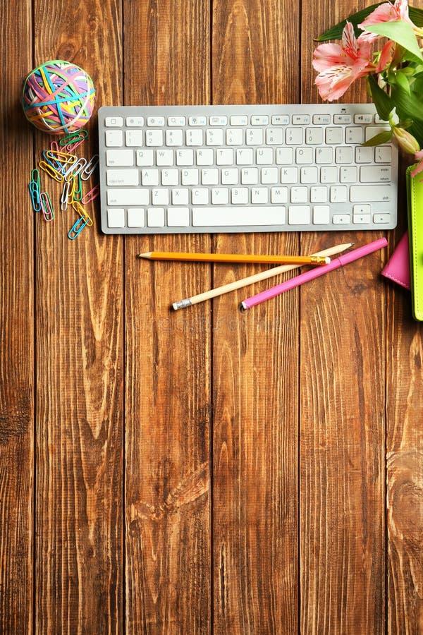 Клавиатура, цветки и канцелярские принадлежности компьютера на таблице, плоском положении Состав рабочего места стоковое изображение rf