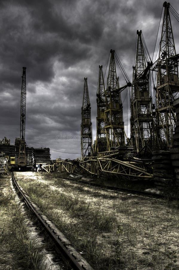 Кладбище кран с поднимающейся укосиной металла с железнодорожными путями и бетонными плитами стоковое фото