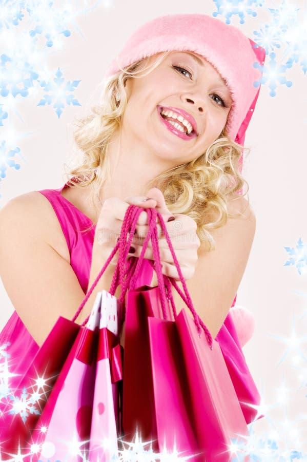 кладет жизнерадостную покупку в мешки santa хелпера девушки стоковое изображение rf