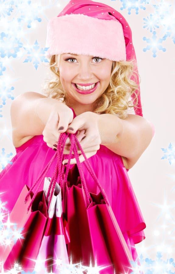 кладет жизнерадостную покупку в мешки santa хелпера девушки стоковое изображение