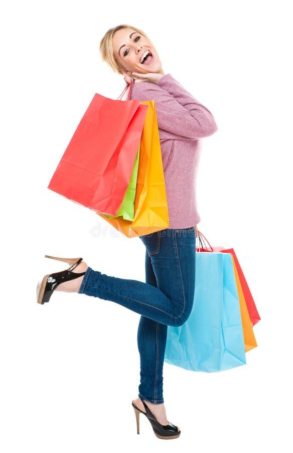 кладет красивейших excited детенышей в мешки женщины покупкы стоковое изображение