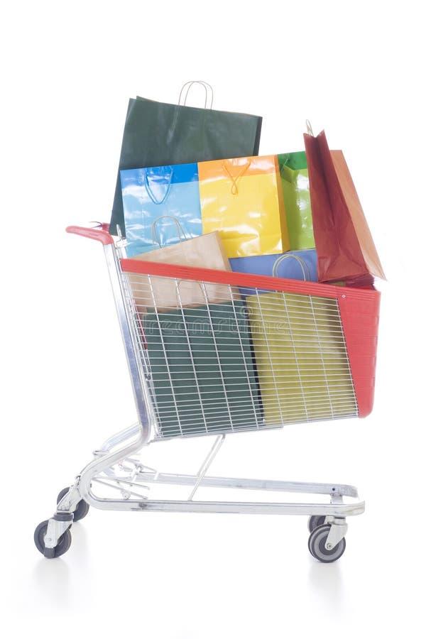 кладет покупку в мешки большой тележки польностью красную стоковое изображение rf