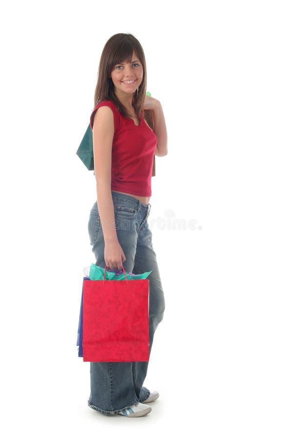 кладет покупку в мешки девушки стоковое фото