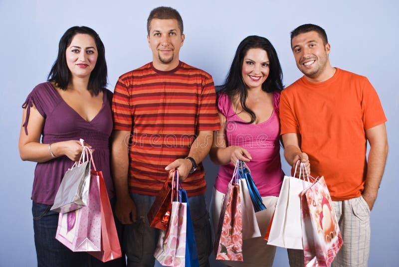 кладет покупку в мешки людей друзей стоковые фотографии rf