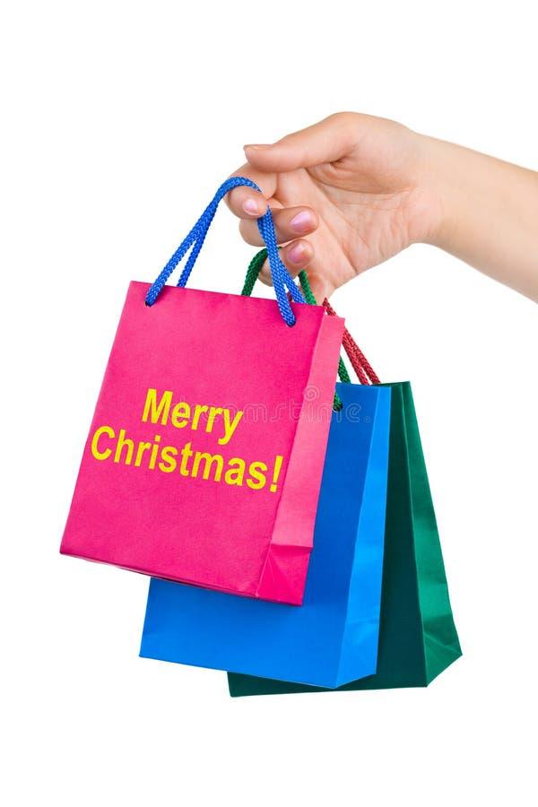кладет покупку в мешки руки рождества веселую стоковые изображения rf