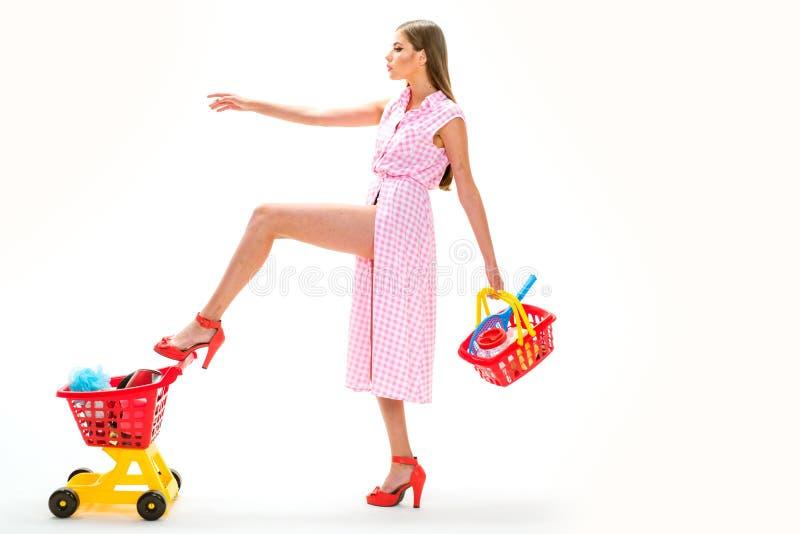 кладет тяжелую в мешки Легкая и быстрая винтажная женщина домохозяйки изолированная на белизне девушка покупок с полной тележкой  стоковая фотография rf