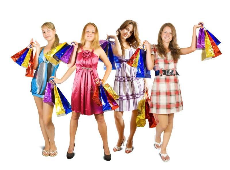 кладет ходить по магазинам в мешки девушок стоковое фото rf
