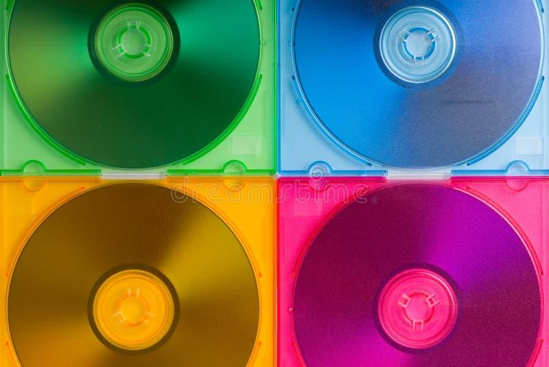 кладет cd диски в коробку цвета стоковые фото